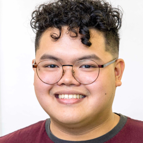 Patrick is a member of the tech team and a partnership advisor. He looks into the camera, smiling, wearing a maroon shirt and circular glasses.