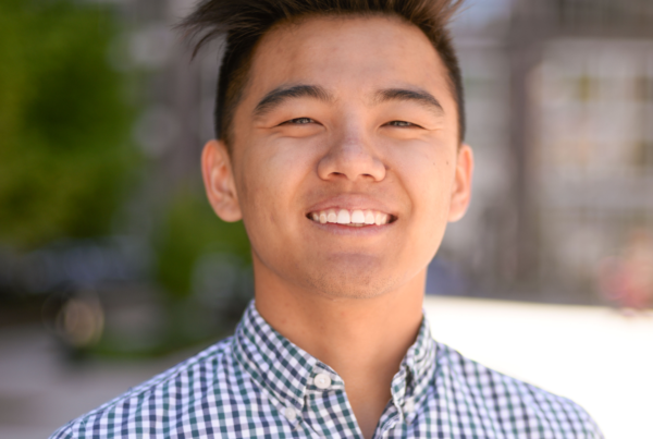 Will Liu, member of the tech team, smiles into the camera, He is wearing a blue checkered shirt