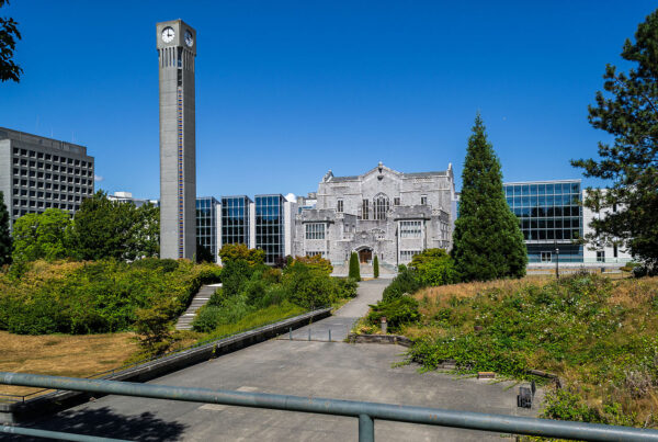 The UBC Campus, where AMS resides. A grey stone building sits behind a tall grey clocktower.
