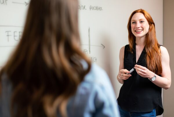 A female tutor with red hair stands infront of a whiteboard and responds to a student's questions.