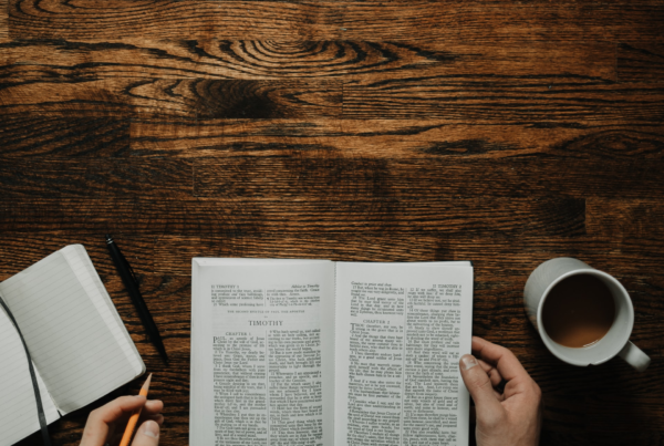 an open book and a coffee mug on a wooden table