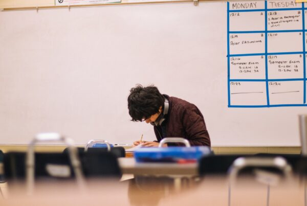 a young male student sitting infront of a blank whiteboard hunches over his work